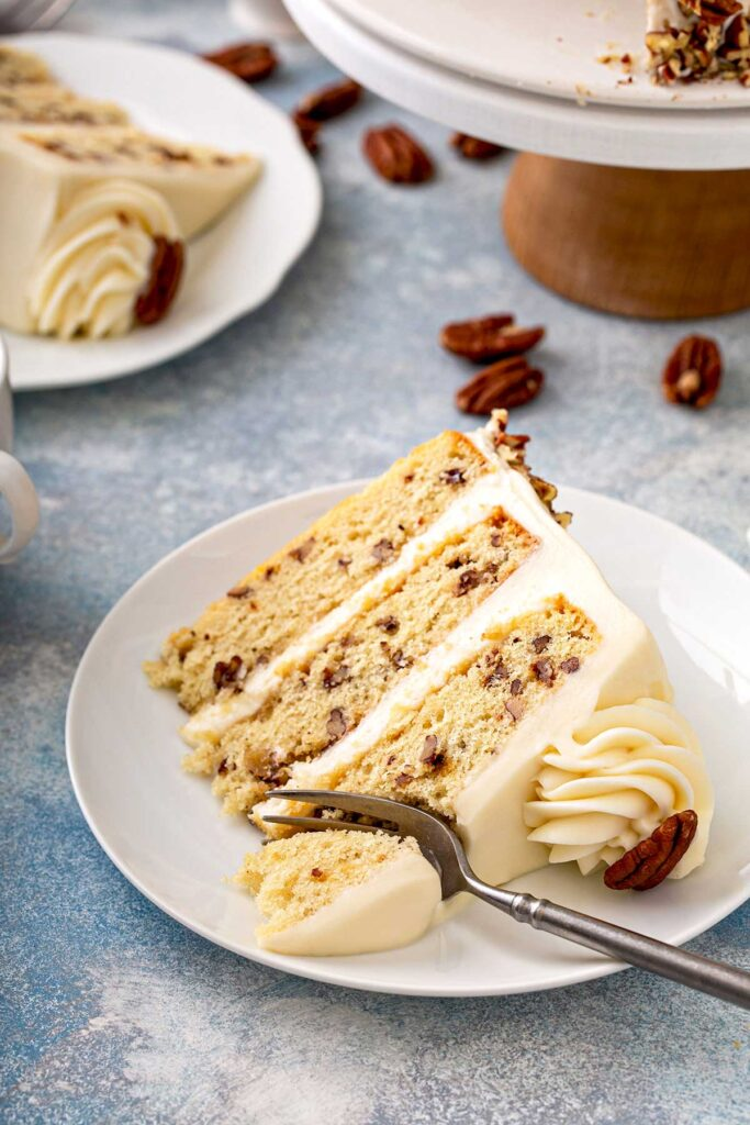 Sliced of layered butter pecan cake on a white plate
