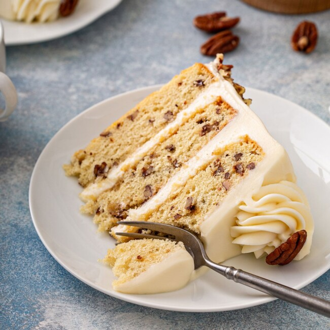 tender and irresistible layered vanilla cake with buttered pecans on a plate