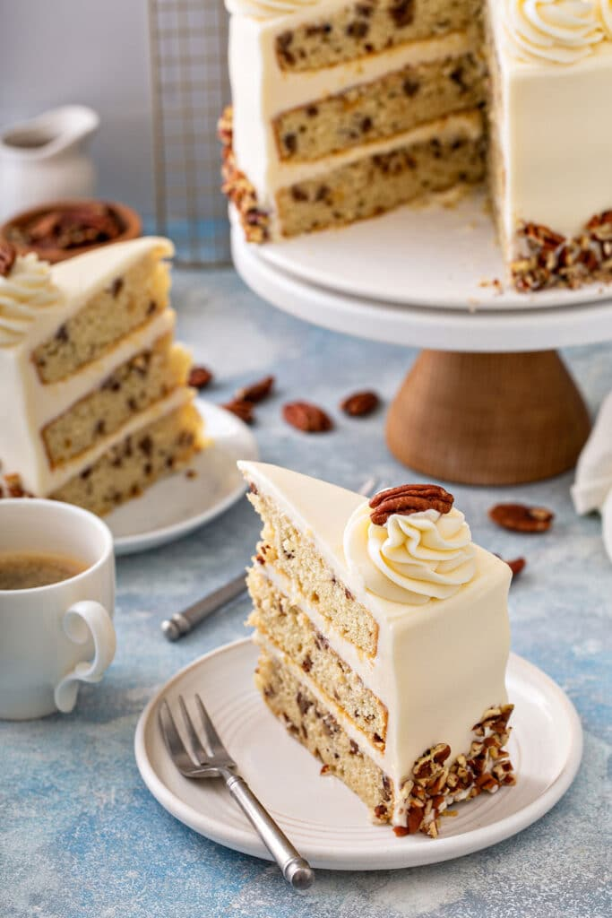 Slices of layered vanilla cake studded with buttered pecans frosted with cream cheese frosting on a white plate