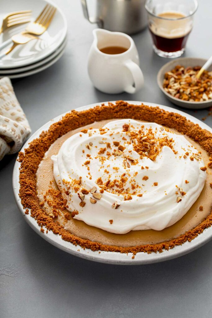 Butterscotch pie topped with silky whipped cream and biscoff cookie crumbs and crunchy pecans
