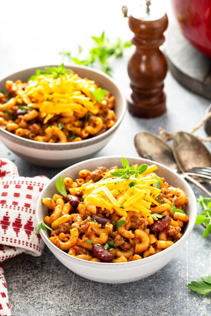 Dinner bowls filled with cheesy chili mac and cheese with chili beans