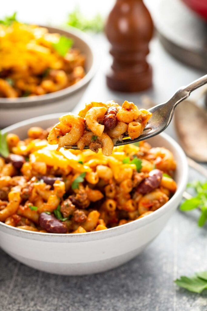 A fork lifting beef chili mac from a dinner bowl.