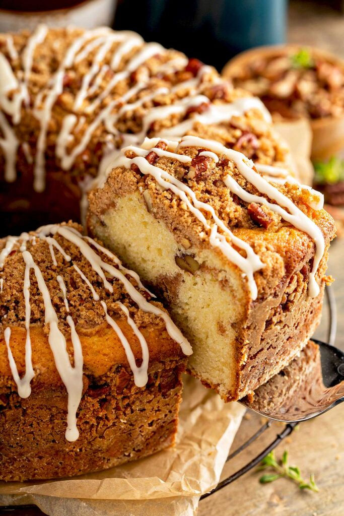 Coffee cake with maple glaze drizzle lifted from a cake platter