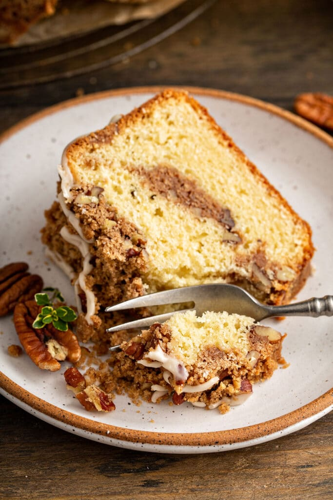 Slice of coffee cake with cinnamon sugar and pecan crumb topping getting cut with a fork
