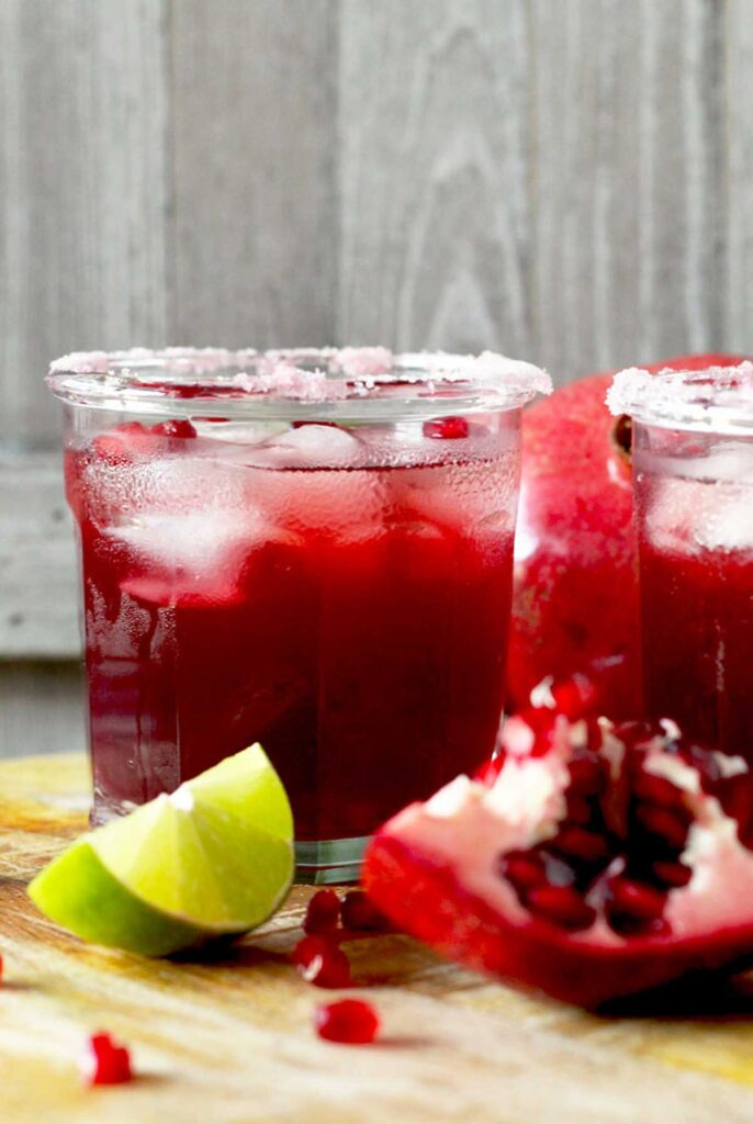 Glass filled with pomegranate margarita on ice