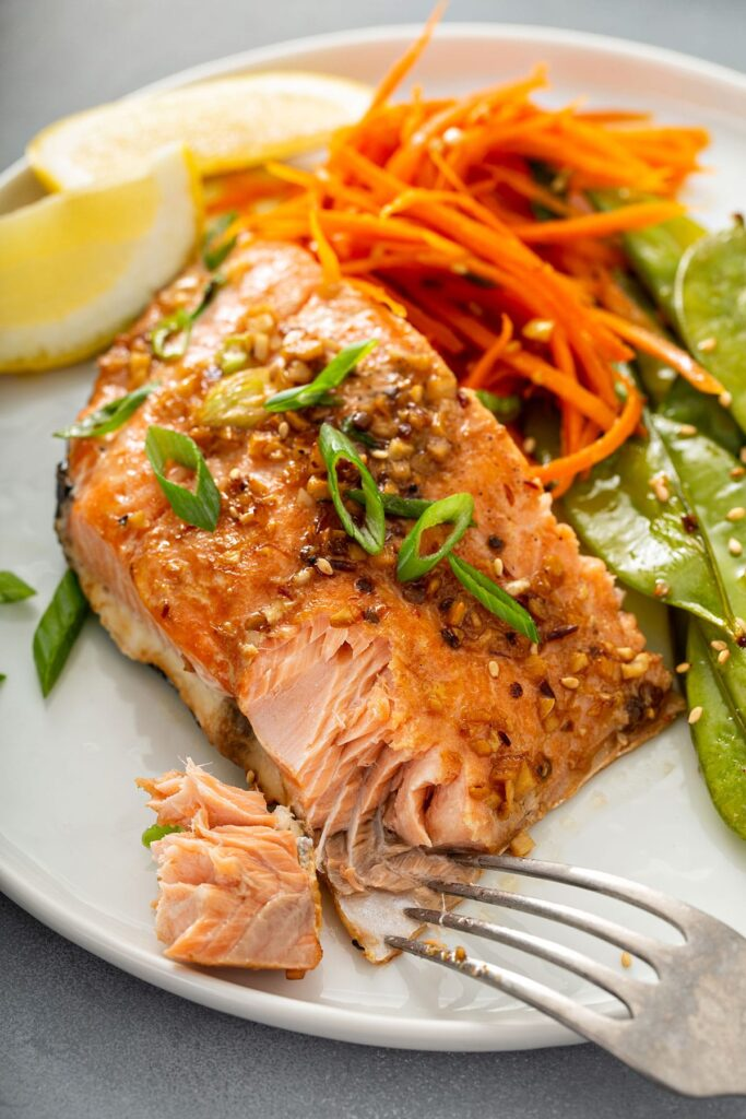 Flakey salmon fillet with veggies served on a white plate.