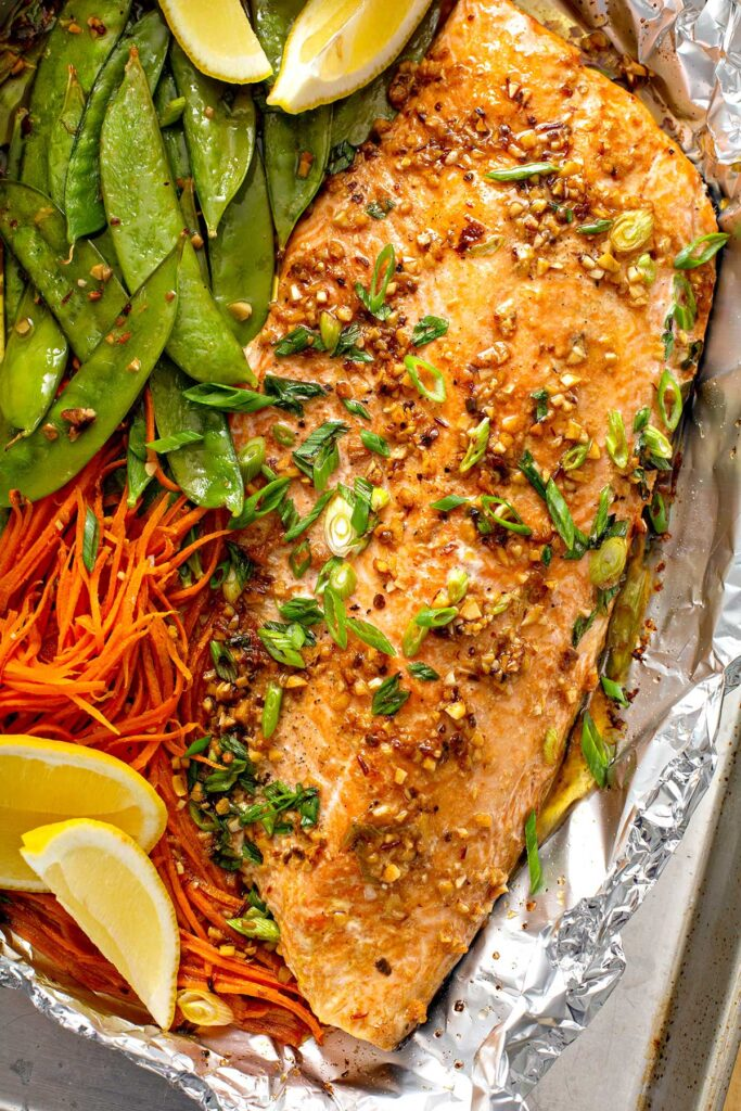 Succulent salmon fillet with shredded carrots and snow peas baked in foil