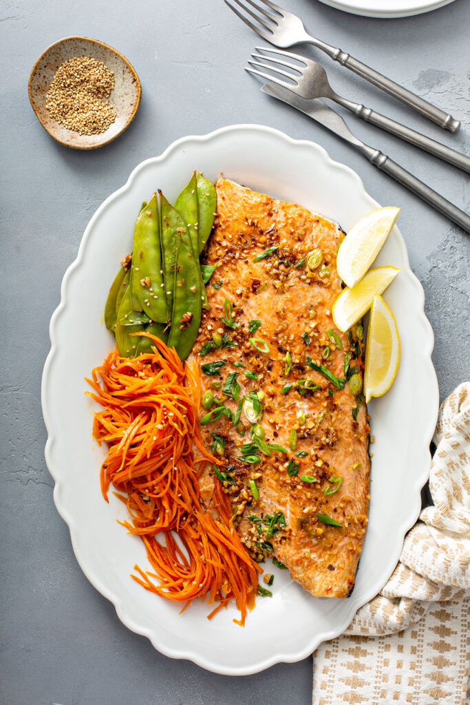A side of salmon with flavored butter, sliced scallions and veggies on a serving platter