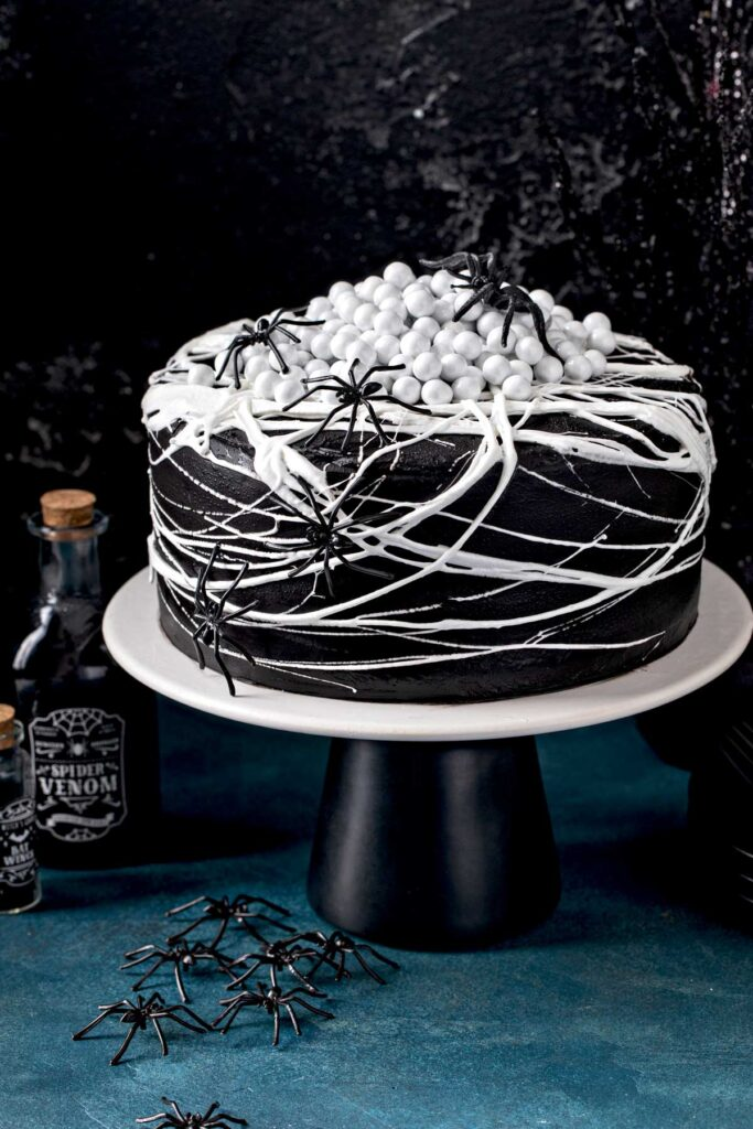 Black velvet cake with black cocoa buttercream, marshmallow spiderweb and black spiders. Topped with candy spider eggs on a cake plate