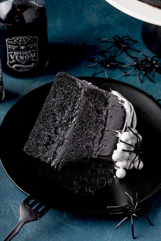 Soft and buttery black velvet cake served on a black plate.