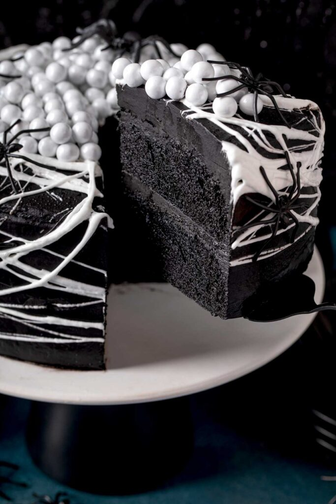 A piece of black velvet cake getting served from a cake stand