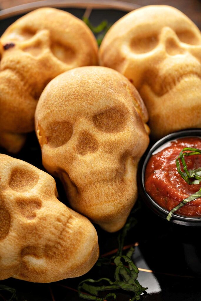 Close view of golden brown pizza skull pockets next to a bowl of pizza sauce.
