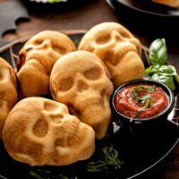 Golden brown baked pizza skulls serves on a black plate for Halloween