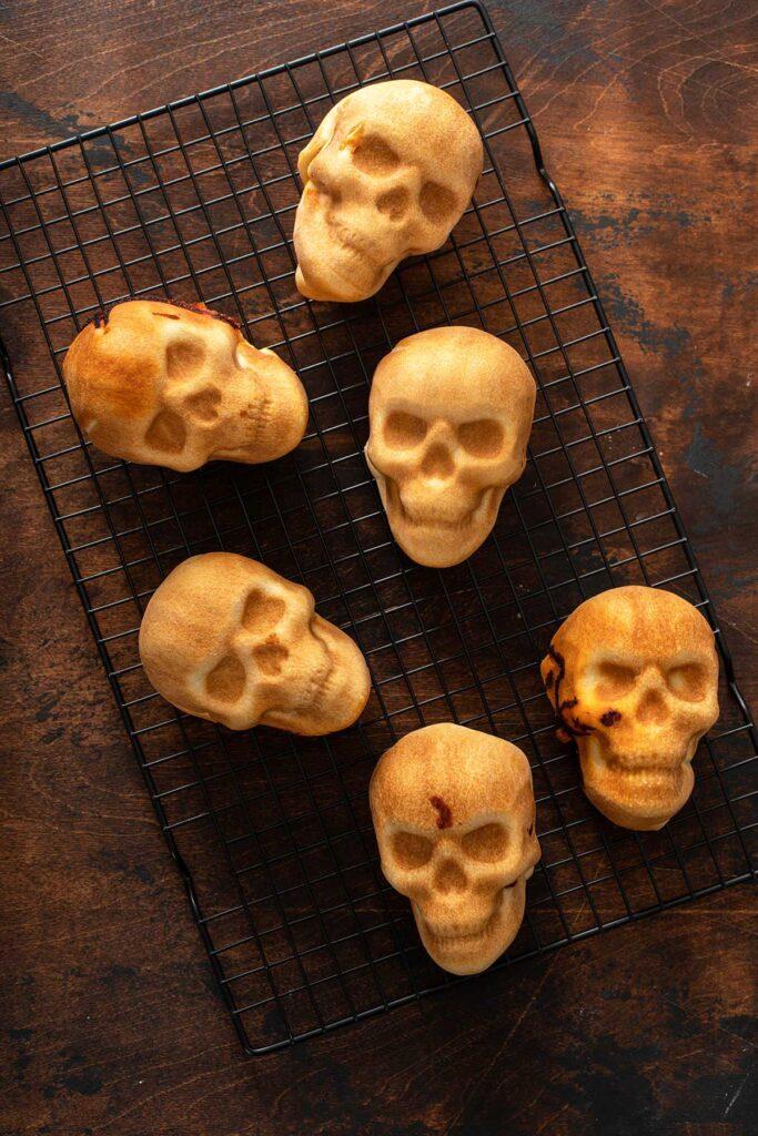 Baked pizza skulls on a cooling rack.