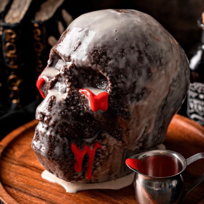 Chocolate cake shaped like a skull and coated with vanilla glaze on a wooden plate.