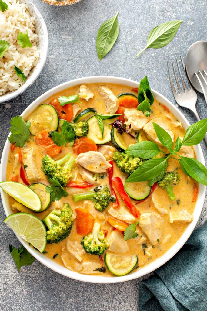 A bowl filled with Thai chicken curry with vegetables garnished with fresh herbs.