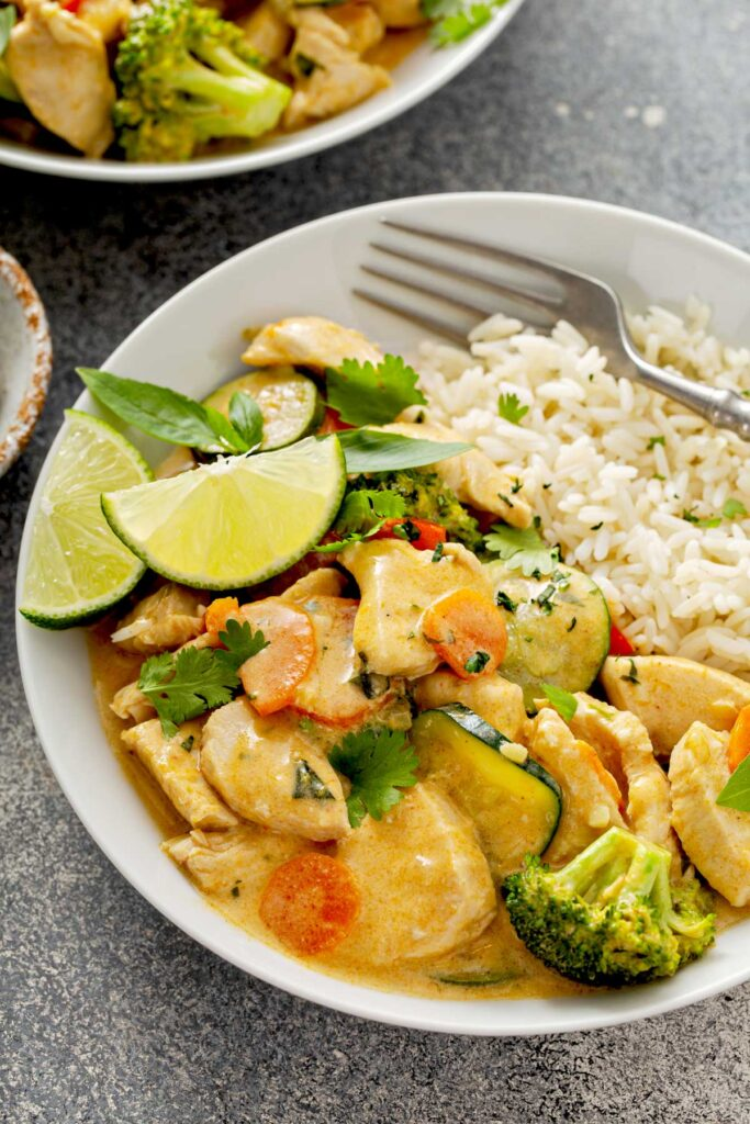 Close view of sliced boneless chicken breast and vegetables in red curry sauce served with rice.